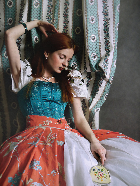 A woman in a victorian outfit, sitting by a decorative curtain, in a dreamy pose, touching her red hair and holding a mirror.
