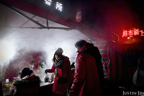 Street stalls erect on the edge of a central Chinese city where rural residents who have lost their land come to eat. <br /> <br /> China is pushing ahead with a dramatic, history-making plan to move 100 million rural residents into towns and cities over six years &mdash; but without a clear idea of how to pay for the gargantuan undertaking or whether the farmers involved want to move.<br />