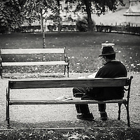 Man with hat sitting on a bench in one of the park gardens in central Budapest reading the daily newspaper
