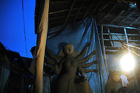 INDIA (West Bengal - Calcutta)  2006, An unfinished Durga idol at a  bylane in kumortuli. Kumortuli in North Calcutta is the hub of Durga idol makers. During the other time of the year the artists engage themselves in prepairing other idols and masks depending on the assignments. But the most of the earning they aquire from making Durga idols. A Durga idol can cost up to 7000 usd. Which is a big price in Indian Currency.  Durga Puja Festival is the biggest festival among bengalies.  As Calcutta is the capital of West Bengal and cultural hub of  the bengali community Durga puja is held with the maximum pomp and vigour. Ritualistic worship, food, drink, new clothes, visiting friends and relatives places and merryment is a part of it. In this festival the hindus worship a ten handed godess riding on a lion armed wth all possible deadly ancient weapons along with her 4 children (Ganesha - God for sucess, Saraswati - Goddess for arts and education, Laxmi - Goddess of wealth and prosperity, Kartikeya - The god of manly hood and beauty). Durga is symbolised as the women power in Indian Mythology.  In Calcutta people from all the religions enjoy these four days of festival in the moth of October. Now the religious festival has become the biggest cultural extravagenza of Calcutta the cultural capital of India. Artistry and craftsmanship can be seen in different sizes and shapes in form of the idol, the interior decor and as well as the pandals erected on the streets, roads and  parks.- Arindam Mukherjee