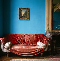 A red velvet curtain is tossed casually over a Regency sofa.in a room painted a powder blue
