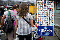 A woman passes a booth promoting Pres. Barack Obama for President on West 135th Street in Harlem in New York during the Harlem Week street fair on Sunday, August 19, 2012.  (© Frances M. Roberts)