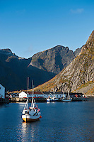 Fishing boat in harbour with mountains in background, Hamnøy, Lofoten Islands, Norway