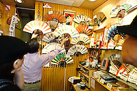 Bunsendo owner Osamu Arai shows customers some of his fans, Asakusa, Tokyo, Japan, August 28, 2011. Sensoji is one of the oldest temples in Tokyo, and the shopping arcades around it have sold visitors souvenirs for centuries.