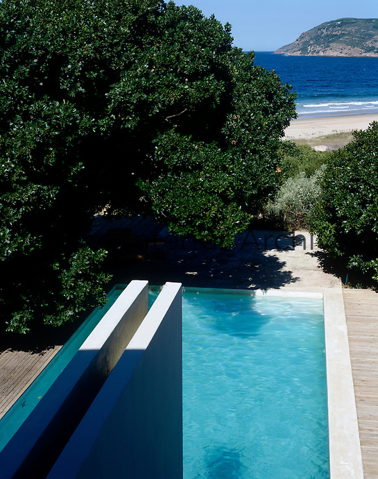 A floating wall which houses a water feature juts out over the swimming pool with a view to the beach beyond