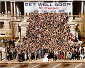 """United States Vice President George H.W. Bush and all the White House staff members with """"Get Well Soon Mr. President"""" sign in front of Old Executive Office Building, next door to the White House in Washington, D.C. on Tuesday, April 7, 1981..Mandatory Credit: Bill Fitz-Patrick - White House via CNP"""