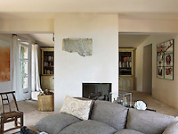 A central chimney breast with contemporary open fireplace divides the living and dining area of the open-plan space