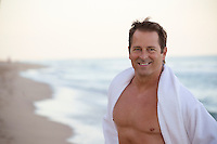 handsome middle aged man without a shirt at the beach in Florida
