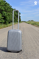 Suitcase on empty countryside road (Licence this image exclusively with Getty: http://www.gettyimages.com/detail/90096557 )