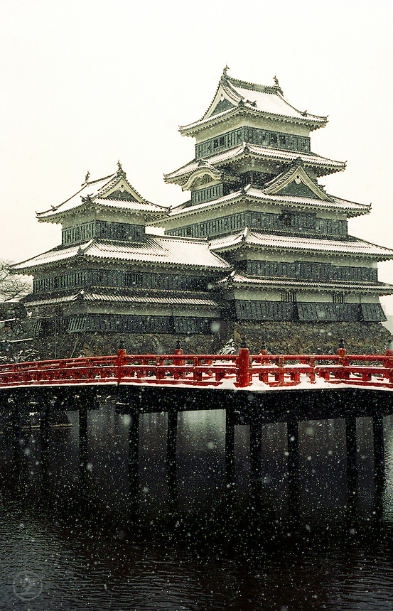 Snow falls on the dark tiles the distinctive vermilion bridge of Matsumoto Castle, Nagano, Japan.