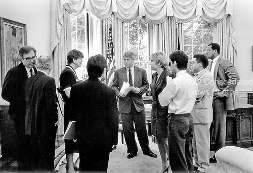 United States President Bill Clinton meets with Attorney General Janet Reno in the Oval Office of the White House in Washington, D.C. on Thursday, June 24, 1993.  White House Counsel Vince Foster, far left, is whispering into the ear of fellow counsel Bernard Nussbaum.  Press Secretary Dee Dee Myers is at the immediate right of The President..Credit: White House via CNP