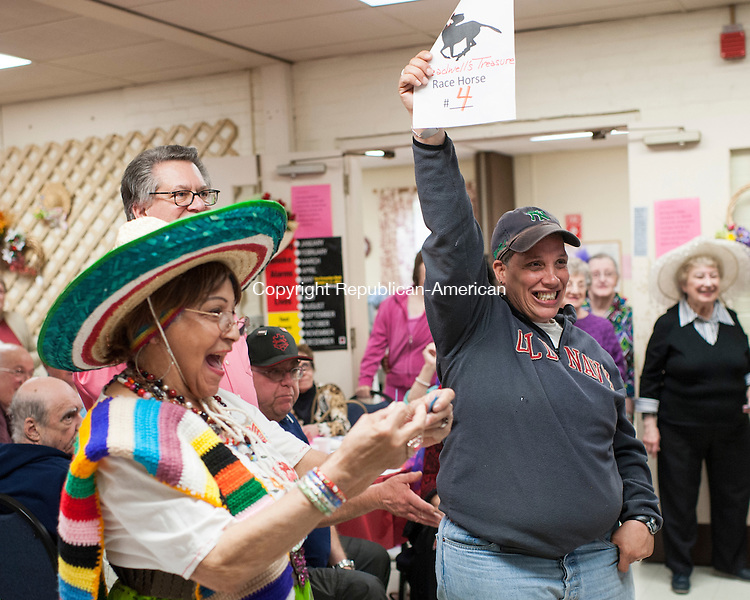 """NAUGATUCK, CT-1 May 2015-050115EC06-  Maritza Bok-Lopez celebrates after being declared the winning """"jockey"""" during Kentucky Derby Day at the Naugatuck Senior Center. Next to her is Vickie Rodriguez, who had a winning ticket. This is the tenth year the senior center marked the Kentucky Derby with it's own friendly competition. Members volunteered to be jockeys and were assigned a horse number. A roll of the dice determined if they advanced to a winning position. The senior center was packed with fancy hats and a Kentucky themed dinner. Members of the U.S. Army handed out roses. Erin Covey Republican-American"""