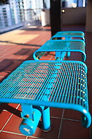 Blue metal benches in a downtown Miami Metromover elevated rail station.