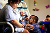 Ludy Rivera, left, a teacher for four years, holds Nathan Cervantes, 6 weeks old, in her arms while Oscar Ochoa, 8 months old, clamors for attention at the Guadalupe Center, which provides child care and literacy programs for families, in Immokalee on Thursday. Bonita Bay residents are hosting their annual Maynard Cup golf tournament and auction this weekend to benefit the Guadalupe Center's Jim Near Center for Family Education. The event last year raised $260,000. Story, Local. Erik Kellar