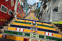 A woman sits on Selaron's Stairs (Escadaria Selarón), a mosaic staircase made of colorful tiles, in Rio de Janeiro, Brazil, 13 February 2012. World-famous staircase, mostly covered by vibrant yellow, green and blue tiles (inspired by the colors of the Brazilian flag), is the masterpiece of Chilean-born artist Jorge Selarón who considers it as a personal tribute to the Brazilian people. Connecting the neighborhoods of Santa Teresa and Lapa, the stairway is made up of 250 steps and measures 125 meters long. In 1990 Selarón began work on the stairway, creating a constantly evolving piece of art, now adorned with over 2,000 brightly colored tiles collected from over 60 countries. Selarón funds his one man's project through donations and the sale of his black-and-red paintings which mostly depict a pregnant African woman or himself. Living his passion, the eccentric 65-year-old artist claims that this crazy and unique dream will only end on the day of my death.