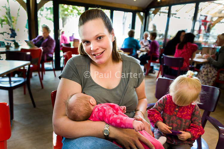 A mother breastfeeds her baby in a cafe with an older sibling playing next to her.<br /> <br /> Date taken: 30/03/2012<br /> Hampshire. England, UK