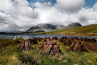 Low angle view of Lough Inagh with the Twelve Bens (Na Beanna Beola), in the background and bales of peat in the foreground, Connemara, Ireland, in the afternoon. Lough Inagh, 7 km long and 1 km wide with a number of wooded islands, is a famous fishing lake. The Twelve Bens or Pins is a range of peaked quartzite mountains. Picture by Manuel Cohen
