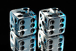 Pair of clear dice isolated on black background with reflection