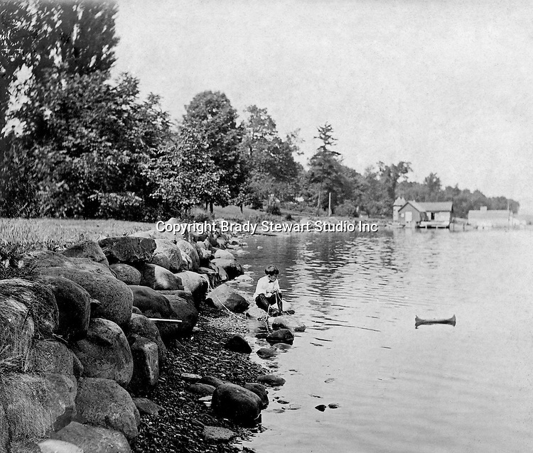 Lakewood NY: Young boy kneeling on the shore and playing with his toy canoe on Lake Chautauqua - 1901. Photographs taken during a church field trip to Chautauqua Institution in New York (Lake Chautauqua). The Stewart family and friends visited Chautauqua during 1901 to hear Stewart relative, Dr. S.H. Clark  speak at the institute. Alice Brady Stewart chaperoned and Brady Stewart came along to photograph the trip.  The Gallery provides a glimpse of how the privileged and church faithful spent summers at Lake Chautauqua at the turn of the century.