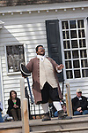 A period actor in Colonial Williamsburg, Virginia shows male visitors how to properly bow.