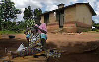 Joyce Candiro braids her friend Agnes Mutone's hair behind Candiro's home in Naguru Estates. in Kampala, Uganda.  The Kampala City Council was planning to sell the land of the estates to developers and gave tennants of the low-income housing area six months to move out. Popular protests stopped the plan. (Rick D'Elia)<br />