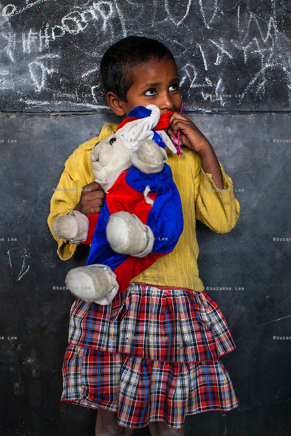 Sofia, 4, poses for a portrait with a soft toy in the Guria Non-Formal Education center in the middle of the Shivdaspur red light district, Varanasi, Uttar Pradesh, India on 20 November 2013. Guria uses the soft toys as a form of therapy for the children of the women in prostitution and also use it as signals of the children's emotional wellbeing.