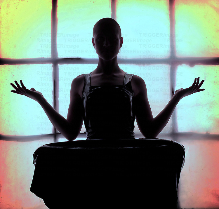 The silhouette of a young woman sitting cross legged meditating