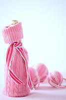 Champagne in a pink knitted bottle cover beside a collection of Christmas baubles