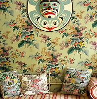 A Native American moon mask hangs against a wall covered in Les Lilas fabric from Le Decor Francais