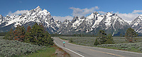 Panorama, Bicycle rider on highway, Teton Mountain Range, Grand Teton National Park, Wyoming, USA.