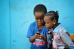 Refugee children use a mobile phone during a break between classes in a school operated by St. Andrew's Refugee Services in Cairo, Egypt. The school is supported by Church World Service.