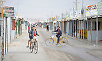 Boys ride bicycles on a street in the Zaatari refugee camp near Mafraq, Jordan. Established in 2012 as Syrian refugees poured across the border, the camp held more than 80,000 refugees by early 2015, and was rapidly evolving into a permanent settlement. The ACT Alliance provides a variety of services to refugees living in the camp.