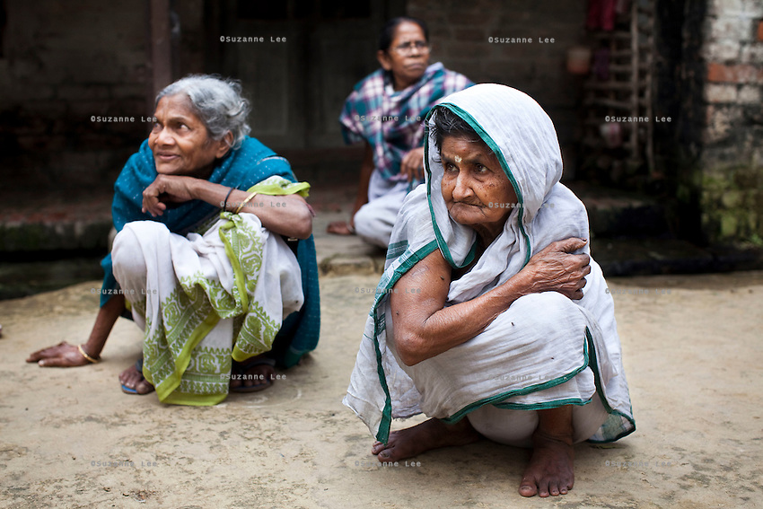 "(L-R: (blue) Saraswati Saha, 84; unnamed; and (white) Kamla Das, 90) Three elderly women who were the original refugees of The Partition recall being brought to Cooper's Camp on trains and trucks as they gather outside their homes in Cooper's Camp, Nadia district, Ranaghat, North 24 Parganas, West Bengal, India, on 19th January, 2012. ""The government will neither eat us nor spit us out."" says Kamla Das. ""They dropped us off here (in 1947) and I'm still here!"" Over 60 years after the bloody creation of Bangladesh in 1947, refugees who fled what was then known as West Pakistan to India still live as refugees, raising their children as refugees, and standing in line for government handouts..Photo by Suzanne Lee for The National (online byline: Photo by Szu for The National)"