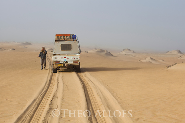 Namibia;  Namib Desert, Skeleton Coast, Northern Skeleton Coast National Park, 4x4 vehicle and tourist on dunes north of Moewe Bay