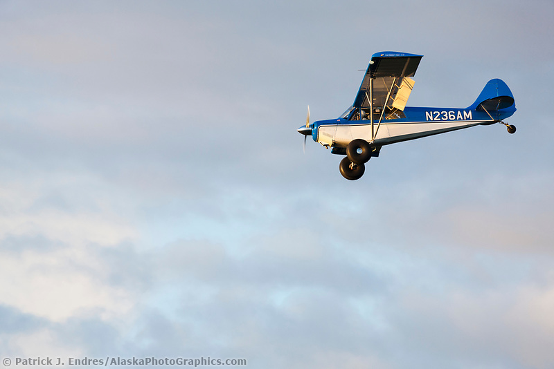 Bush plane on wheels approaches for landing on airstrip near Lake Hood, Anchorage, Alaska.