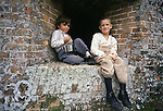Six-year-old Dwayne Mathews, left, and Nathan Church, 7, sit in a gun port after the Battle of Fort Morgan, Mobile, Al in 2001. Jim Bryant Photo. @2001. All Rights Reserved.