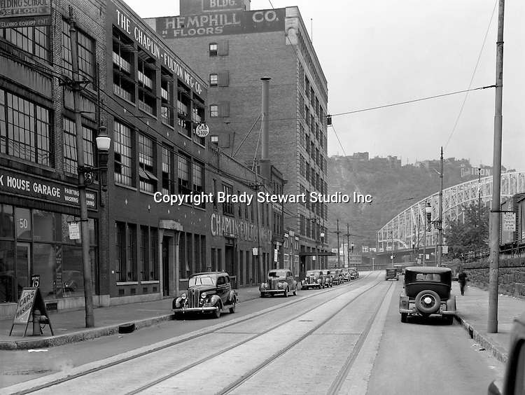 "Pittsburgh PA:  View looking west on Penn Avenue toward the Point Bridge - 1935.  Point Bride in the background along with the famous ""Drink Iron City"" sign."