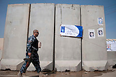 KIRKUK, IRAQ:  An Iraqi policeman walks past a T-wall protecting the entrance to a polling station in Kirkuk...Security is tightened in the volatile Iraqi city of Kirkuk the day before the national elections.  Kirkuk is home to Kurds, Arabs, and Turkmen and has been so violently divided that the city could not participate in the 2005 elections.