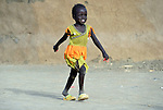 A displaced girl runs in Agok, a town in the contested Abyei region where tens of thousands of people fled in 2011 after an attack by soldiers and militias from the northern Republic of Sudan on most parts of Abyei. Although the 2005 Comprehensive Peace Agreement called for residents of Abyei--which sits on the border between Sudan and South Sudan--to hold a referendum on whether they wanted to align with the north or the newly independent South Sudan, the government in Khartoum and northern-backed Misseriya nomads, excluded from voting as they only live part of the year in Abyei, blocked the vote and attacked the majority Dinka Ngok population. The African Union has proposed a new peace plan, including a referendum to be held in October 2013, but it has been rejected by the Misseriya and Khartoum. The Catholic parish of Abyei, with support from Caritas South Sudan and other international church partners, has maintained its pastoral presence among the displaced and assisted them with food, shelter, and other relief supplies.