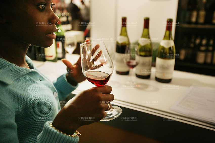 Switzerland. Canton Bern. Bern. A young black african woman tastes and enjoys a glass of red wine during the wine fair at the BEA expo. © 2006 Didier Ruef