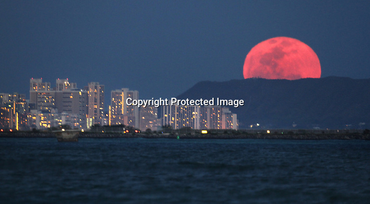 The April full moon rose over Waikiki Diamond Head mountain in Oahu, Hawaii.