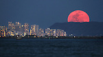 The April full moon rose over Waikiki Diamond Head mountain in Oahu, Hawaii.