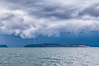 A waterspout touches down behind Hat Island in Tulalip Bay, Washington.  Two other funnel clouds are forming but do not reach the water.