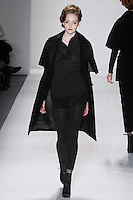 Model walks runway in a black cotton corduroy capelet-trench, black handloomed cashmere/silk pullover w/attached baby corduroy shirt-tail + leggings, from the Zang Toi Fall 2012 &quot;Glamour At Gstaad&quot; collection, during Mercedes-Benz Fashion Week New York Fall 2012 at Lincoln Center.