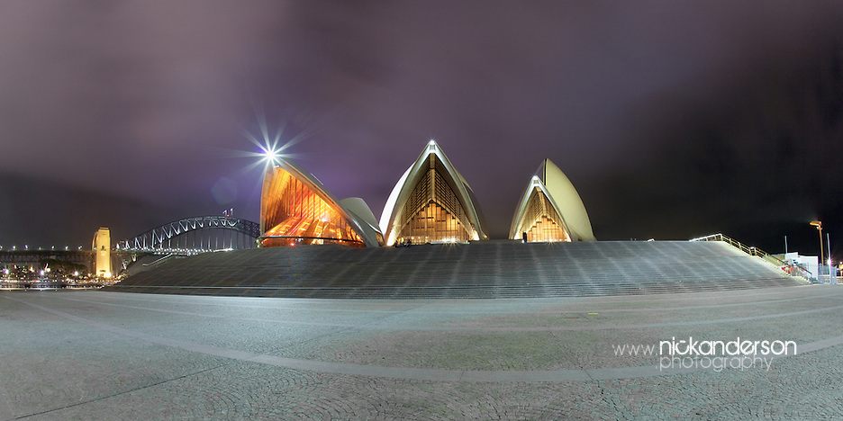 The southern face of Sydney Opera House at night, with Sydney Harbour Bridge in the distance behind (Nick Anderson)