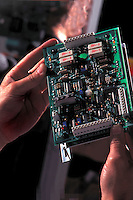 Examining circuit board.<br /> <br /> Larger JPEG + TIFF images available by contacting use through our contact page at :..www.photography4business.com
