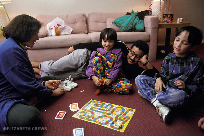 San Diego CA Nuclear family, Mexican father, playing game together at home, children age 5 and 8