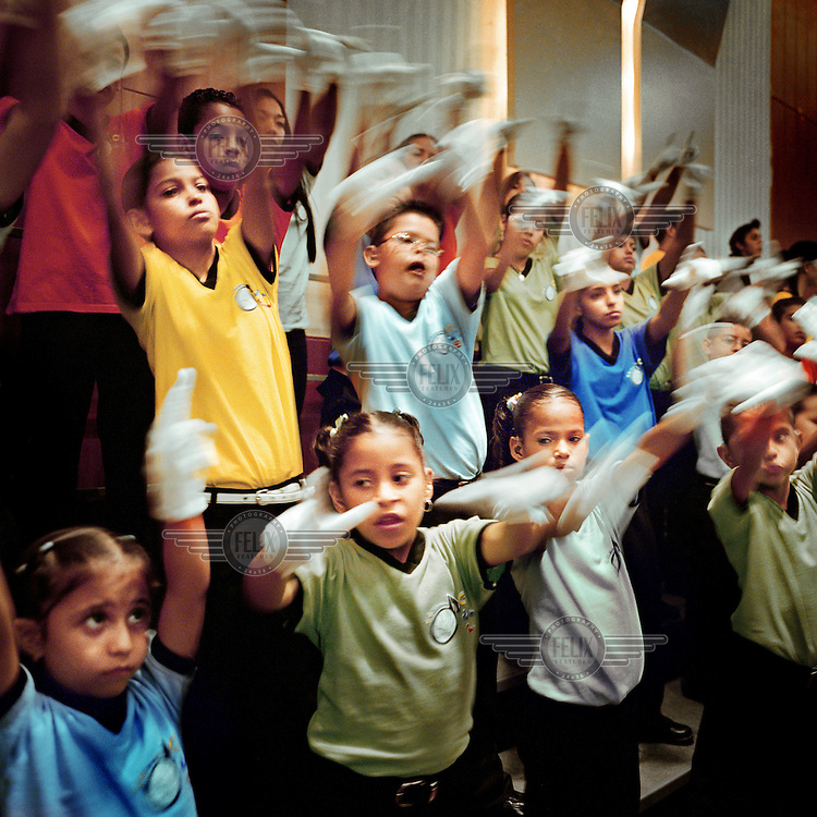 The 'White Hands Chorus', a chorus made up of deaf children who 'sing' with their hands, at the Barquisimeto theatre. 275,000 pupils, most of them under 18, take part in Maestro Jose Antonio Abreu's 'El Sistema'. It was dreamed up in 1975, in his own basement, and has been exported to 23 countries. 85 percent of the students involved come from the poorest areas of Venezuela, and for many it has proved to be a personal salvation, proving to themselves and their communities that music can play a huge role in alleviating the strains of poverty..