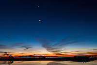 Venus, a bright dot in the sky, over the waxing crescent moon, and both float over a sunset painting the sky and waters of San Francisco Bay at the San Leandro Marina.