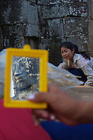 These local Khmer girls sometimes perform the Khmer ASARA dance for tourists at the Bayon temple, here they are at the end of the day taken of their make-up and I ccaught one of the faces from the bayon temple in the mirror.
